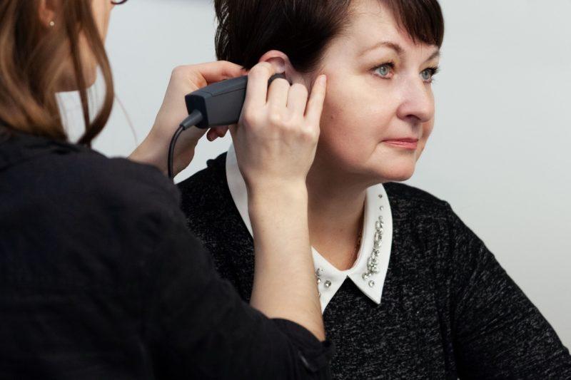 Das Bild zeigt eine Kundin bei der Analyse des Gehörganges