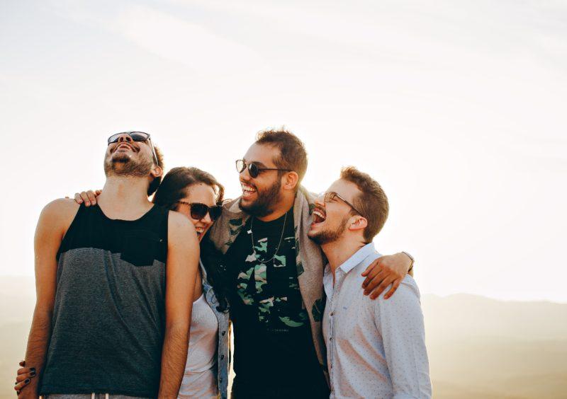 Auf dem Bild sind vier lächelnde Menschen mit Sonnenbrillen zu sehen