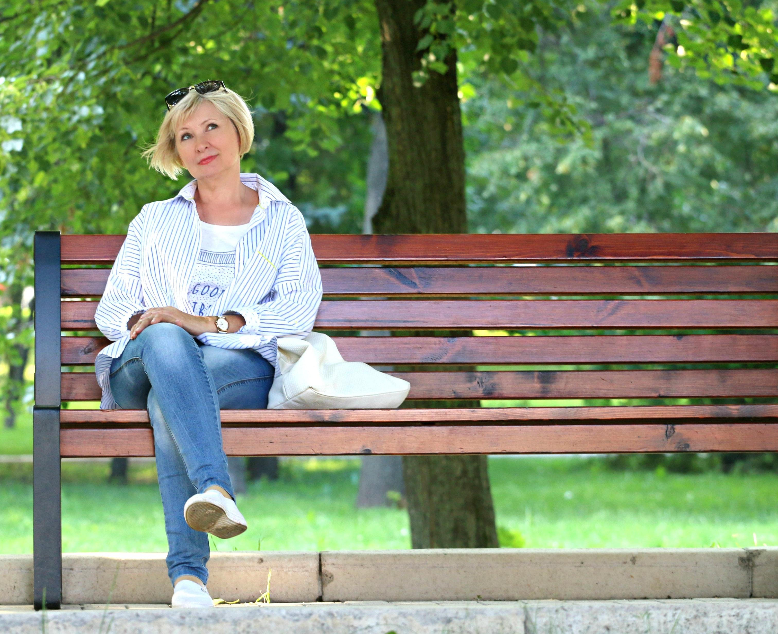 Multifokale Kontaktlinsen. Das Bild zeigt eine Frau auf einer Bank mit einer Sonnenbrille im Haar