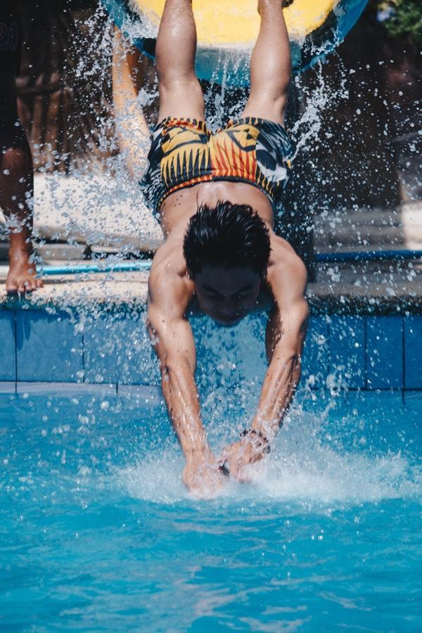 Das Bild zeigt einen Mann bei einem Sprung ins Wasser. harte Kontaktlinsen könnten hier verloren gehen.