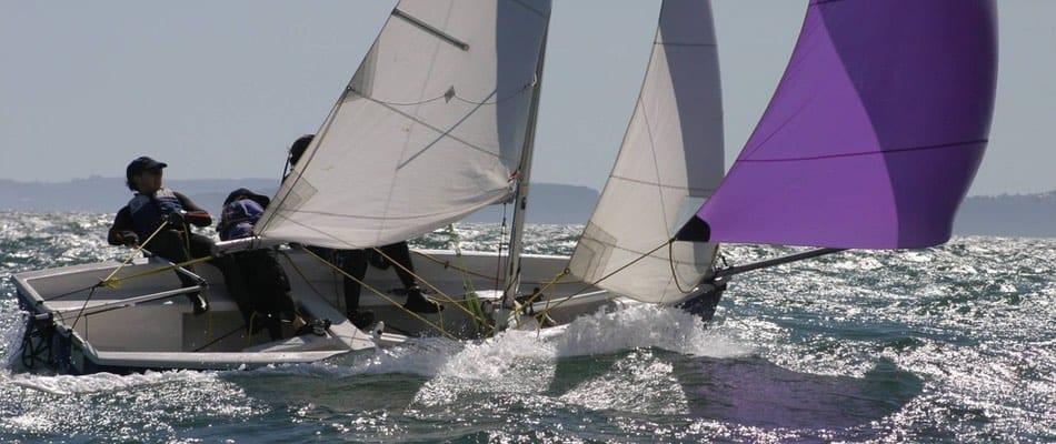 Das Bild zeigt einen Segler und blendende Reflexe auf dem Wasser