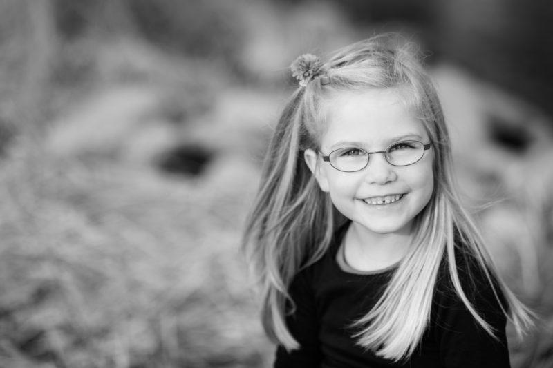 Das Bild zeigt ein blondes Mädchen mit einer Brille im Gesicht