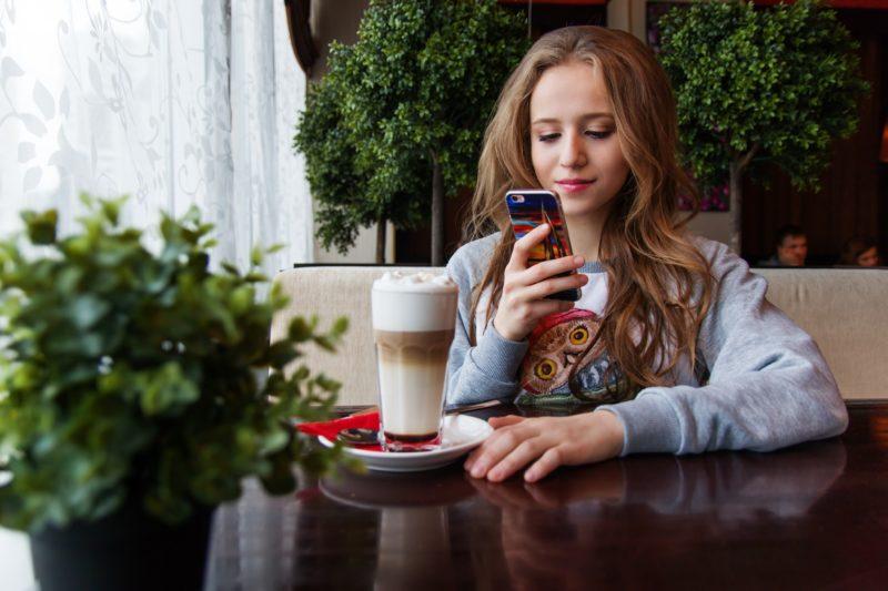 Das Kind zeigt ein Mädchen, das auf ihr Smartphone schaut